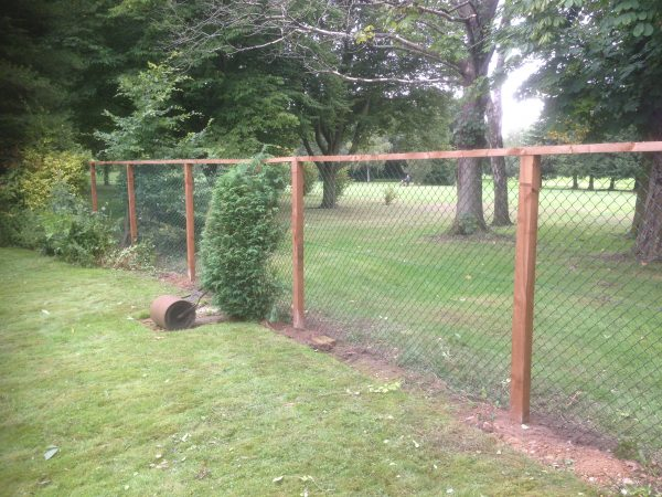 Green chain link fencing with wooden fence posts.
