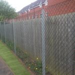 Chain link fencing alongside a public walk way. Commercial fencing provides quality security.