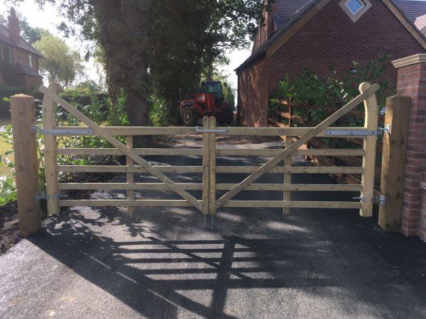 A closed five bar field gate. Two wooden posts stand at either side. The gate is used for commercial purposes on a farm.