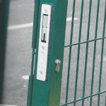 Green wire mesh gate with secure locking system.
