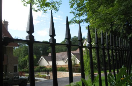 Black steel bespoke railings. These bespoke railings surround a large garden giving it a high quality finish.