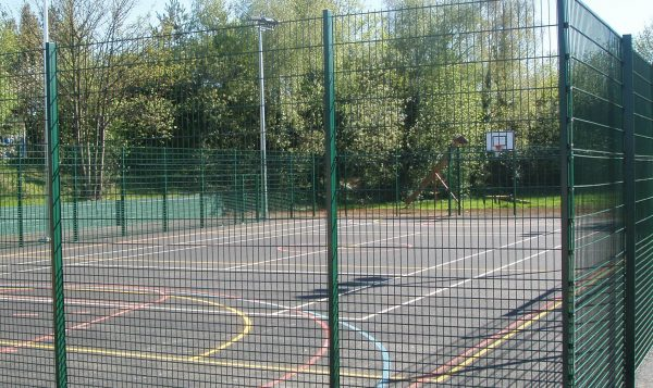 Multiple use games area in a school are park yard. Sport area fit with goal posts and basketball nets.