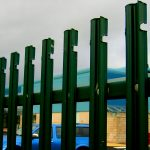 Green steel palisade fencing surrounding a commercial building.
