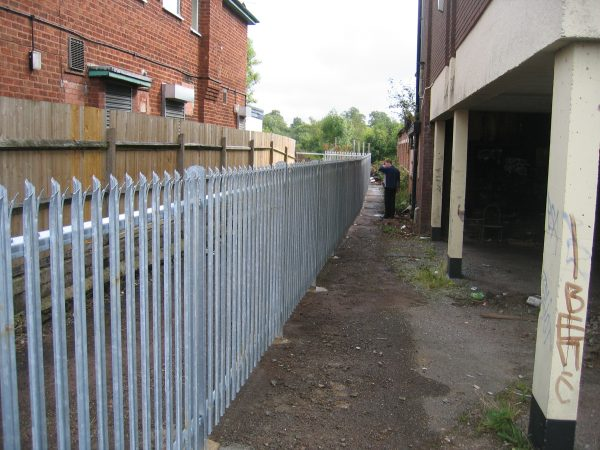 Steel palisade fencing is being assembled by Hodges & Lawrence staff. Commercial fencing provides quality security.
