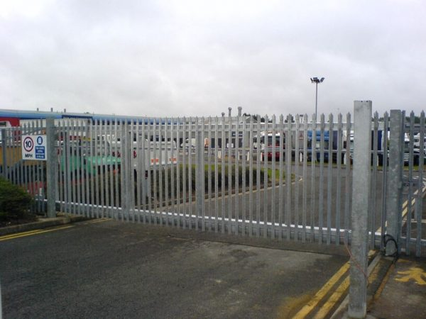 Steel palisade gates gate securing large vehicles in yard. These commercial gates are great for securing industrial spaces.