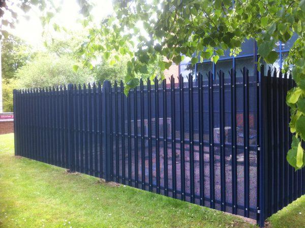 Blue steel palisade fencing surrounding industrial supplies.