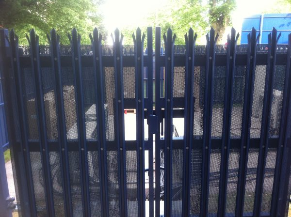 Blue steel palisade gates. These secure commercial gates keep electrical goods safe.