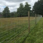A long fence with round fence posts. The fence stands on a empty field.