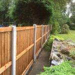A long wooden fence in a garden in Birmingham. The fence has close board fence panels.