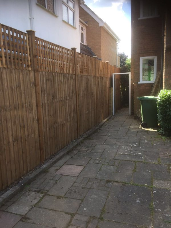 A wooden fence alongside a house in Birmingham. It is a v type fence with close board fence panels.