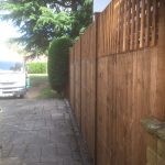 A wooden fence next to a large vehicle. It is a v type fence with close board fence panels.