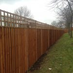 A large wooden fence in an open area. The fence has t type timber trellis fencing panels.