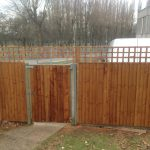 Tall wooden fence. The fence has t type timber trellis fencing panels.