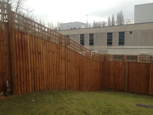 A large open space surrounded by a wooden fence. The fence has t type timber trellis fencing panels.