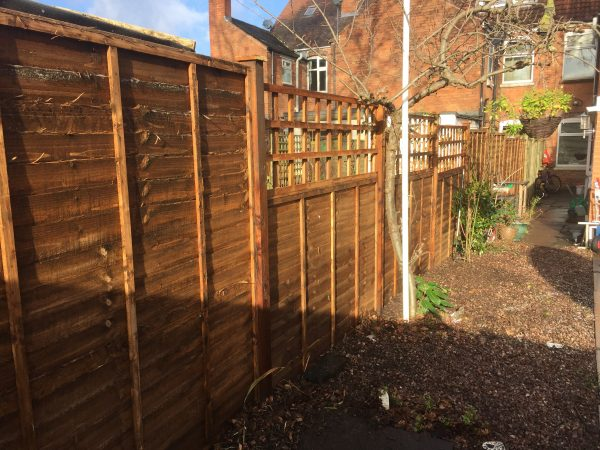 Wooden fence with v type fence panels double framed, horizontally overlapped with bevelled capping.