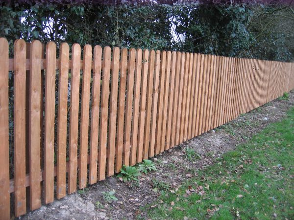 A long wooden fence constructed with timber pales.