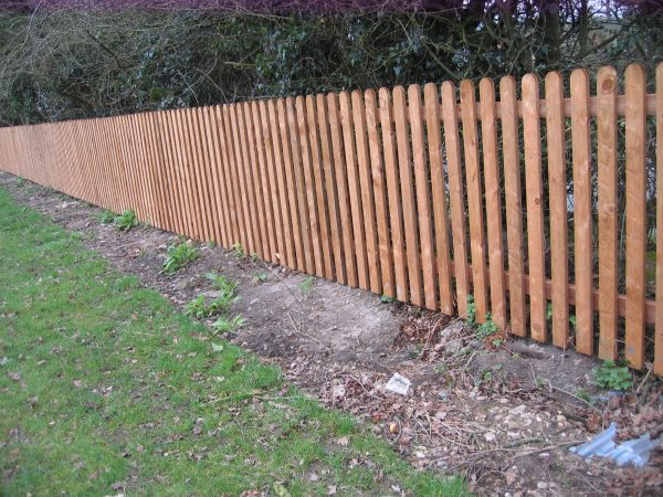 A wooden fence made up with timber pales.