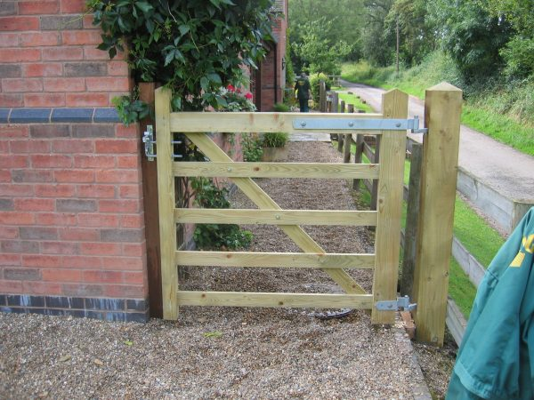 A five bar field gate securing a private property. The field gate is being supported by timber gate posts.