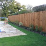 A large garden with a pool and large fence. The fence has feather edge boards and is pressure treated.