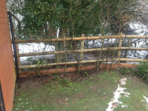A fence runs along the side of a house. The fence has round fence posts and half round fence posts.