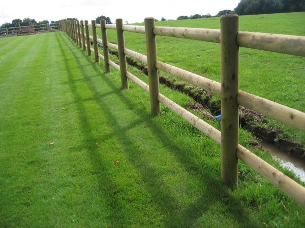 A open field with a commercial fence. The fence has round fence posts and half round fence posts.