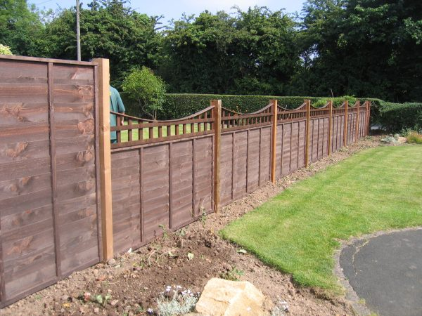 A large garden with a wooden fence. The fence has z type timber panels double framed, horizontally overlapped with bevelled capping.