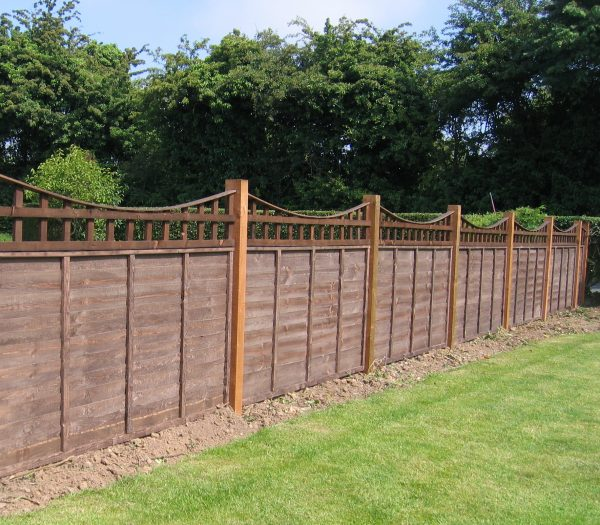 A long wooden fence with z type timber panels, double framed, horizontally overlapped with bevelled capping.