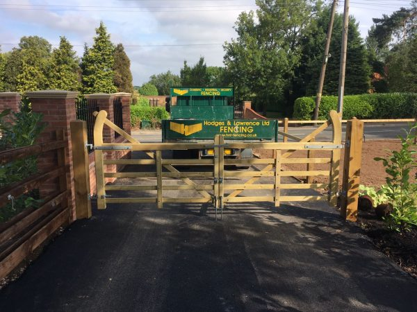 A field gate, newly installed on a yard supported by timber gate posts.
