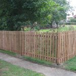 A wooden fence surrounding a large garden or allotment. The ween fence is made up many timber pales.
