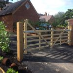 Houses with a long drive. The drive includes a field gate to protect the properties. The gate has supporting timber posts.