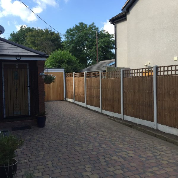 A house and garden with a wooden fence around the perimeter. The fence has v type close board fence panels.