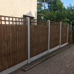 A wooden fence in a garden yard. The fence is v type fence with close board fence panels.