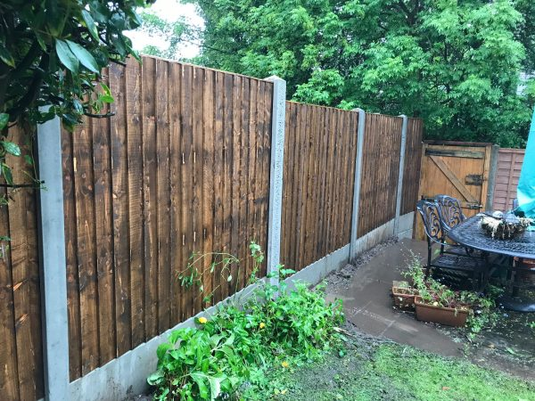 A garden yard with a wooden fence and a steel table. The fence has v type close board fence panels.