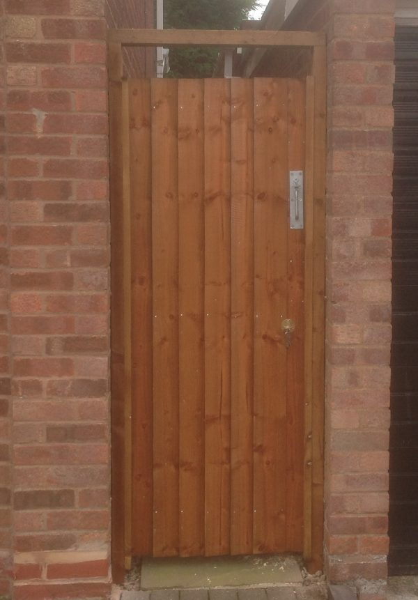 A wall with a gate in the middle. The gate has feather edge boards with a pre-clad timber frame.