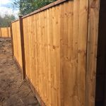 Pressure treated timber posts supporting wooden fence panels surrounding a empty area.