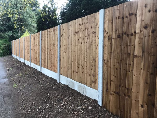 A wooden fence alongside a public walkway. The fence has close board fence panels.