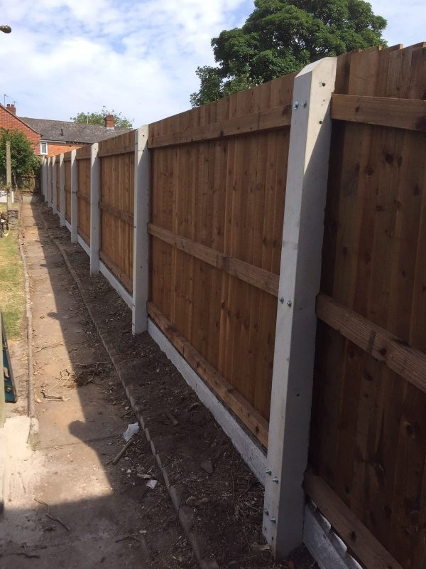A wooden fence with multiple panels and concrete fence posts.