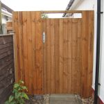 A wooden gates stands at the side of a house. The gate has feather edge boards with a pre-clad timber frame.