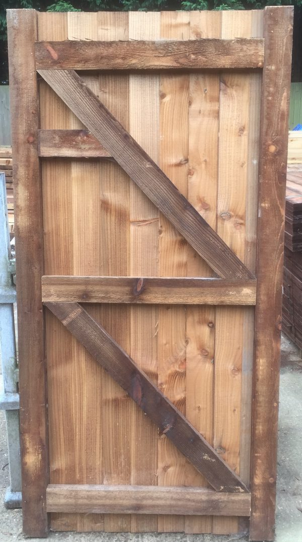 Garden gate held in place with wooden gate frames.