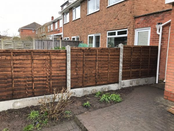 A house with a wooden fence alongside. The fence has z type timber panels which are double framed, overlapped with bevelled capping.