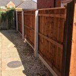 Concrete fence posts support four wooden fence panels on a empty garden.