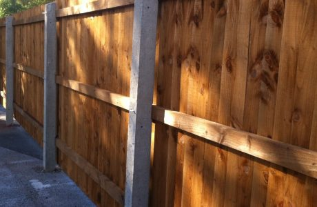 Concrete fence posts supporting wooden fence panels. The fence is on display in a supply yard in Birmingham.