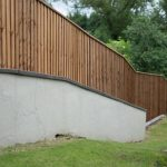 A large open area with a long fence. The fence has feather edge boards and is pressure treated.