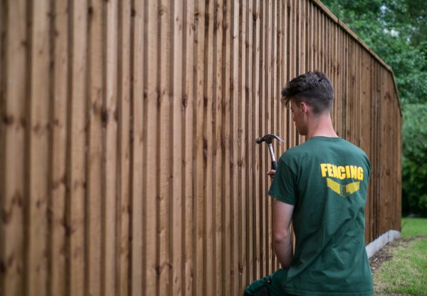 Hodges & Lawrence staff assembling a fence in a garden in Birmingham. The fence has feather edge boards.