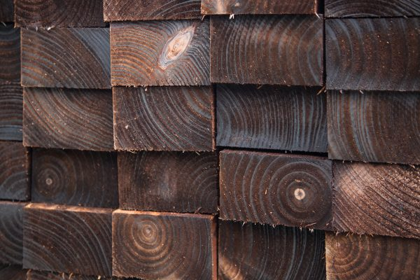 Pressure treated timber. The wood is dark in colour and is displayed in a fencing suppliers in Birmingham.