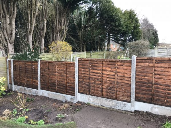 Garden fence. The fence has z type timber panels double framed, horizontally overlapped with bevelled capping.