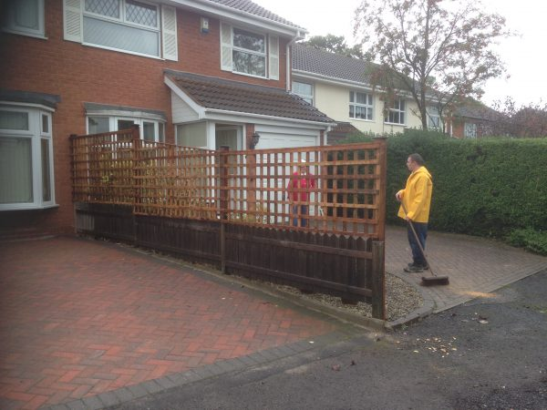 Two people stand behind a wooden fence. The fence has t type timber trellis fencing panels.