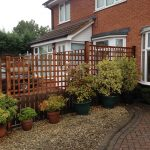 A fence dividing two houses in Birmingham. The fence has t type timber trellis fencing panels.