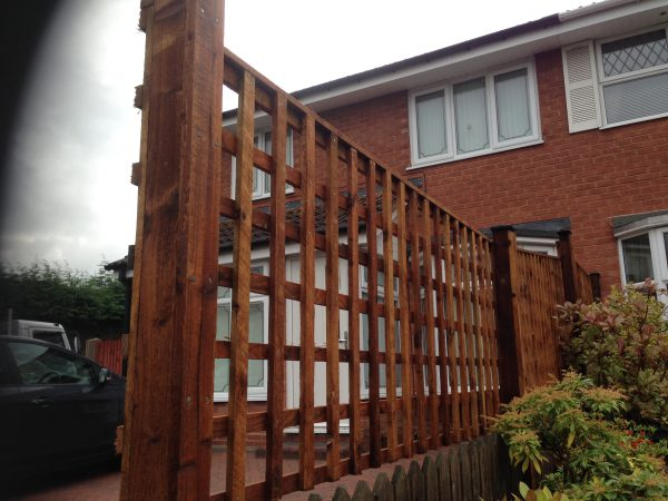 A fence divides two houses. The fence has t type timber trellis fencing panels.
