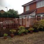 Wooden fencing alongside a house. The fence has t type timber trellis fencing panels.